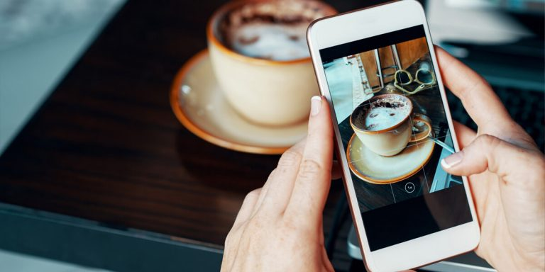 pessoa fotografando uma xícara de café com smartphone